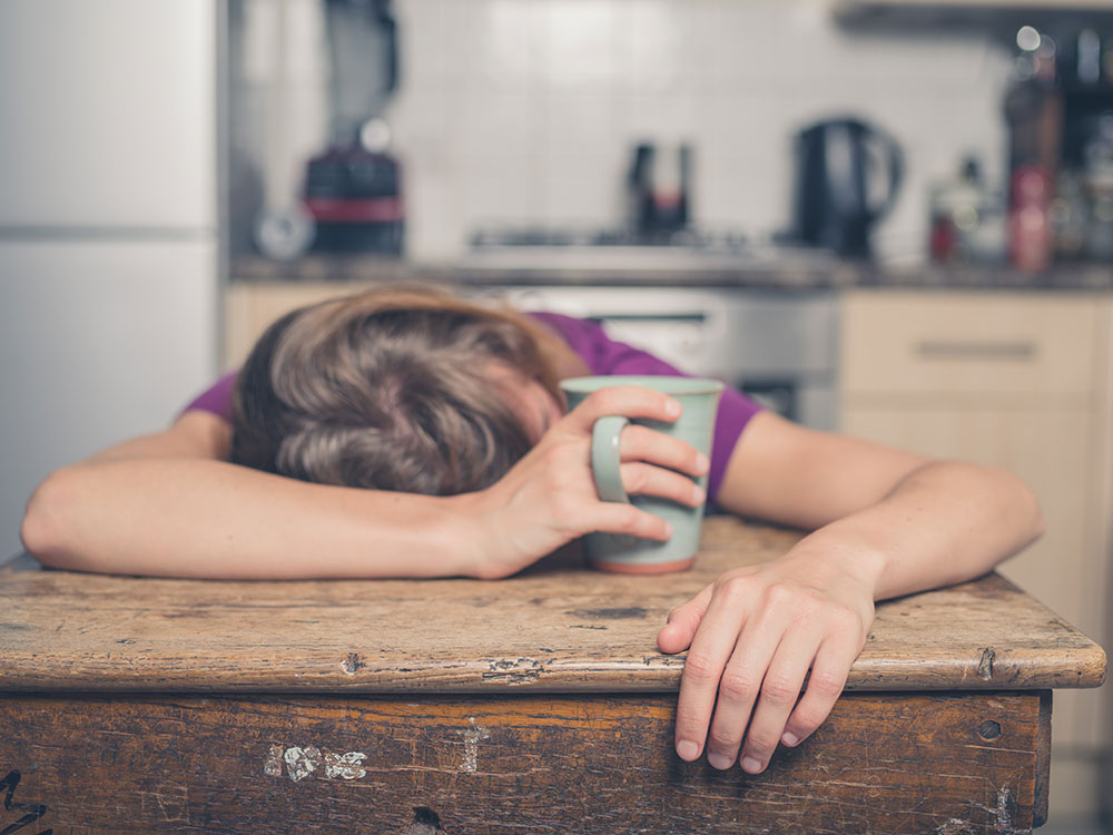 Girl sleeping at kitchen table with coffee in hand