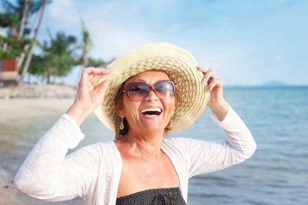 woman smiling on the beach wearing a hat